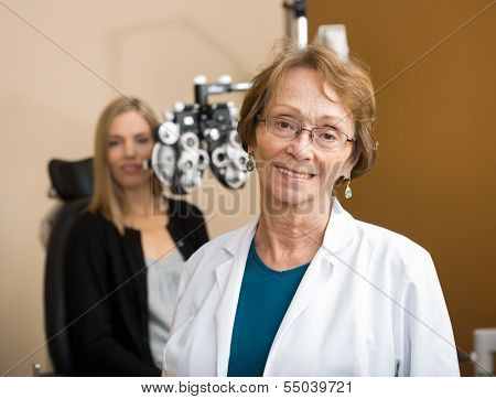 Portrait of senior female optometrist with patient in background