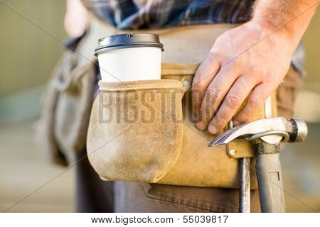 Closeup of disposable coffee cup and hammer on carpenter's tool belt outdoors