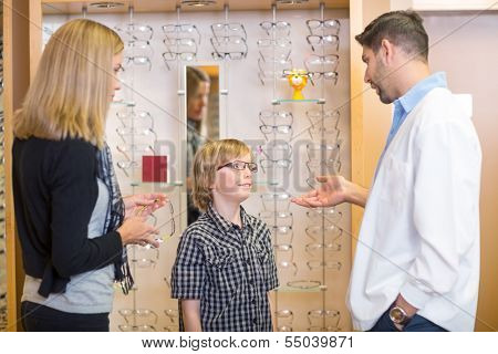 Mid adult male optometrist talking to customers in store