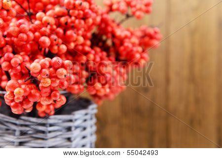 Artificial berries, in wicker vase,  on wooden background