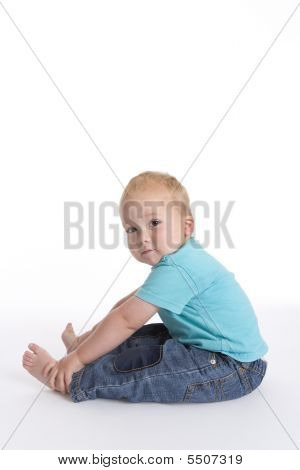 Toddler Boy Sitting On The Floor Holding His Feet Like A Gymnastic Exercise