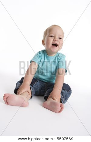 Toddler Boy Sitting On The Floor Holding His Feet And Is Laughing