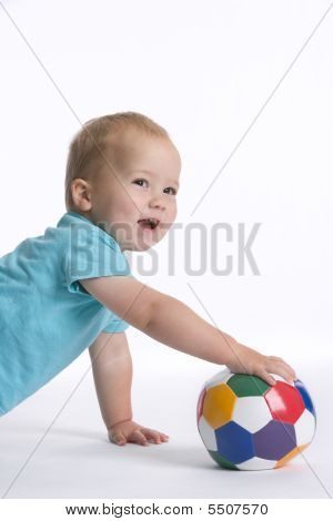 Toddler Boy Crawling On The Floor With A Colored Ball