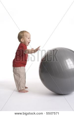 Baby boy with a large ball with an exited expression