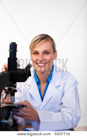 Blonde Scientist With A Microscope Smiling At The Camera