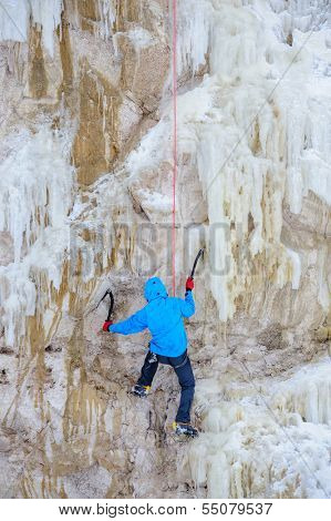 Young man climbing the ice using ice axe