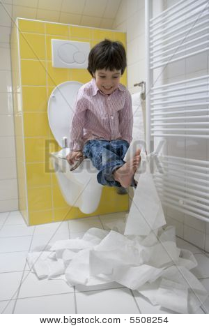 Little boy makes a mess with toilet paper in the bathroom