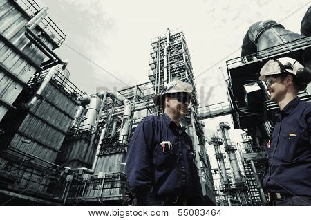 two oil and gas workers with large refinery in background