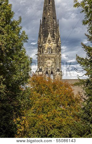 Old Church Steeple In Stormy Weather, Behind Some Autumn Trees