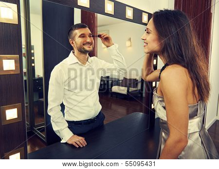 smiley woman looking at man in the mirror
