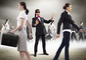 stock photo of blindfolded man  - Image of businessman in blindfold walking among group of people - JPG