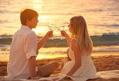 Honeymoon concept, Man and Woman in love, Couple enjoying glass of champagne on tropical beach at su