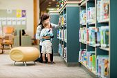 stock photo of kneeling  - Full length of teacher and boy selecting book from bookshelf in library - JPG