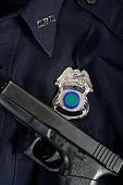 pic of glock  - Handgun laying on blue police uniform with badge - JPG