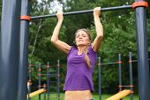 foto of pull up  - Young beautiful girl performing pull ups on the outdoor sports ground - JPG