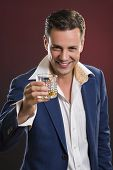 stock photo of swagger  - Portrait of happy smiling stylish businessman wearing blue suit cheering with a glass of alcohol against dark red background - JPG