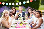 stock photo of dress-making  - Group Of Friends Enjoying Outdoor Dinner Party - JPG