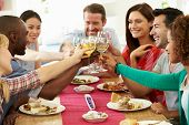 stock photo of proposal  - Group Of Friends Making Toast Around Table At Dinner Party - JPG