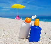 stock photo of suntanning  - detail of two suntan lotion bottles on the sand - JPG