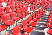 pic of bleachers  - Red chairs bleachers in large stadium - JPG