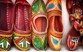stock photo of flea  - Colorful ethnic shoes on flea market in India - JPG