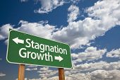 picture of stagnation  - Stagnation or Growth Green Road Sign Over Dramatic Clouds and Sky - JPG