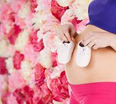 pregnancy, maternity and health concept - belly of a pregnant woman with pink baby booties