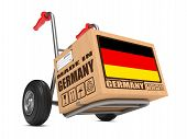 foto of free-trade  - Cardboard Box with Flag of Germany and Made in Germany Slogan on Hand Truck White Background - JPG