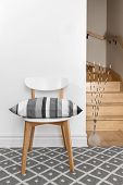 pic of staircases  - Chair decorated with gray striped cushion in a room with staircase - JPG