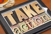 take action - motivation concept -  text in vintage letterpress wood type on a digital tablet