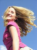 stock photo of titillation  - teen with hair flying and a fun look - JPG