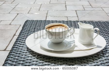 Cappuccino Served With Extra Milk On A Plate