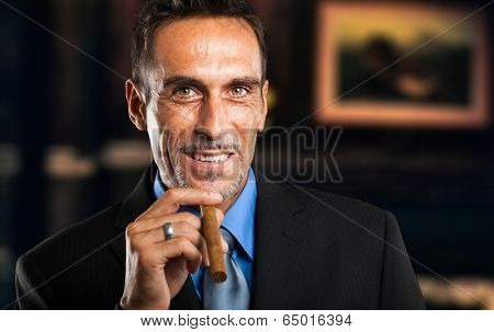 Mature businessman smoking a cigar in a classy room