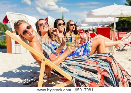 Four woman lying on beach lounger, tanning in the sun