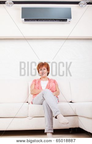 Woman under the air conditioner at home. Happy mature woman on sofa
