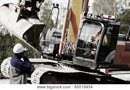 building worker directing large bulldozer and driver