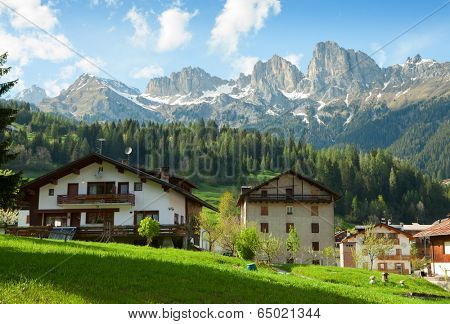Houses are surrounded by the Dolomites, Comune di Falcade, Italy. Houses are surrounded by the Dolomites, Comune di Falcade, Italy. View of a typical alpine residential structure.