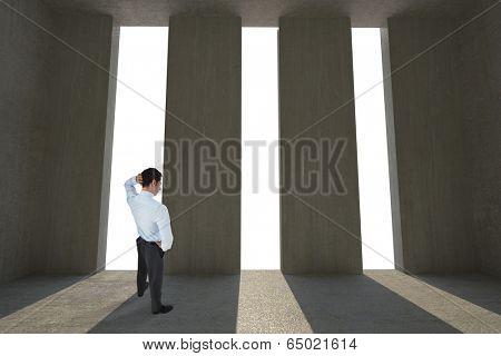 Thinking businessman scratching head against light shining into dark room