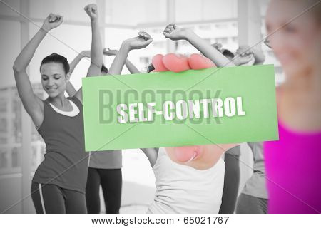 Fit blonde holding card saying self control against fitness class in gym