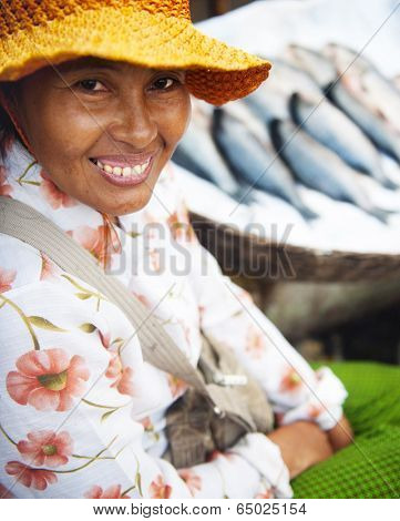 Indigenous cambodian woman selling fish in a market.