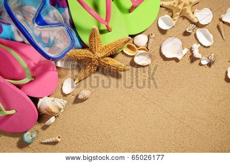Summer holiday setting with flip flops,diving goggles and seastars on beach