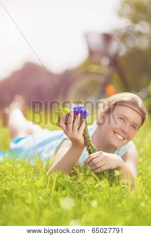 Young Charming Smiling Light-haired Woman Lies On Green Grass In Summer Park With Flowers Bouquet