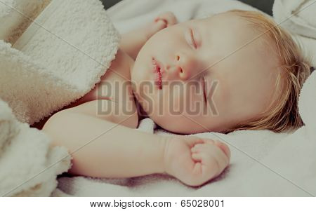 two months old baby sleeping in bed at home