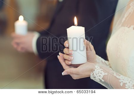 The groom and the bride with candles. Wedding ceremony in church