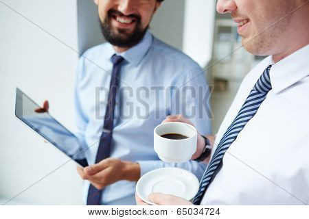 Image of young businessman holding cup of coffee while listening to his colleague at meeting