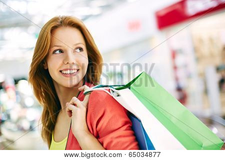 Portrait of happy girl with shopping bags in trade center