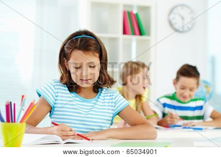 Portrait of lovely girl drawing at workplace with schoolmates on background