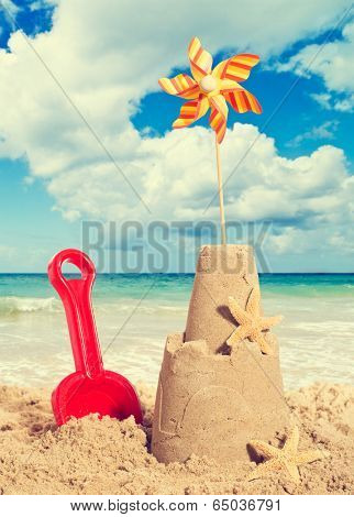 Sandcastle on the beach with pinwheel and starfish - vintage filter effect