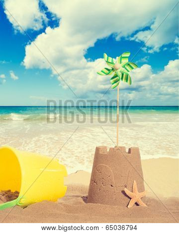 Sandcastle at the seaside with pinwheel and starfish