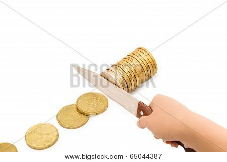 Knife Cutting A Pile Of Coin. Concept Of Budget Cuts, Savings, Recession